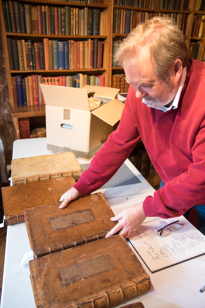 The curator at Little Hall Lavenham returning the books to the shelves